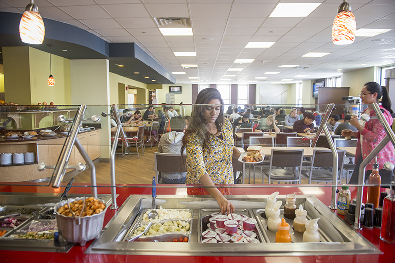 Adelphi student grabbing food from the salad bar at Post Hall